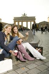Zwei junge Frau mit Einkaufstaschen, sitzen auf dem Bürgersteig