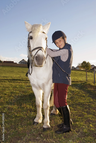 Girl (10-12) standing by pony, portrait