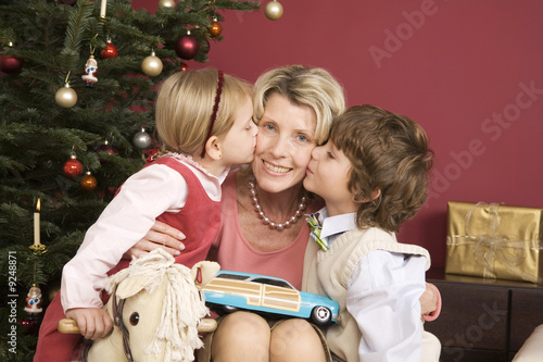 Grandchildren (3-7) kissing grandmother on Christmas eve