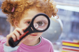 Girl (8-9) looking through magnifying glass, close-up