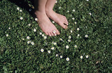 Feet on grass with daisy flowers, close-up