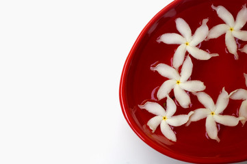 Jasmine petals in water in a red bowl in a spa