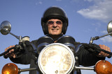Man on motorbike smiling, portrait