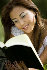 girl reading a book lying on the grass - outdoors