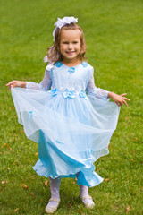 portrait of little girl in blue dress on the green grass