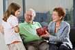 grandparents giving gift to grandchild at home