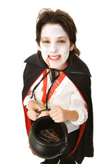 Cute adolescent boy dressed as a vampire for Halloween