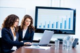 Young businesswomen sitting by meeting table at office poster
