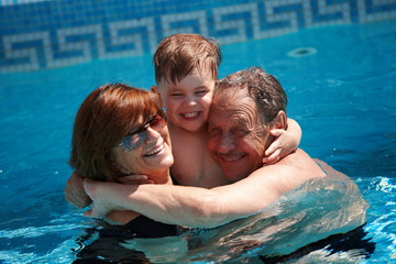 grandparents having bath in pool together with grandson