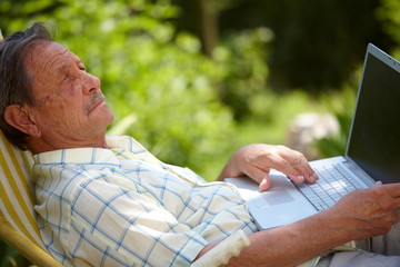 Healthy senior man is his elderly 70s sitting outdoor in garden