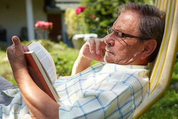 Healthy looking senior man is his late 70s sitting in garden