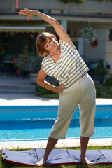 Happy active senior woman doing workout exercise at home