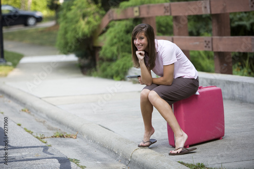 female traveller waiting with her suitcase