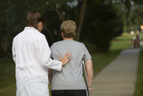 physical therapist helps a woman on crutches poster