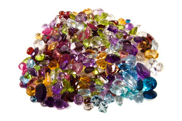 A large group of faceted gemstones on a white background
