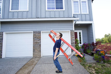 man standing in front of house holding ladder. Horizontal