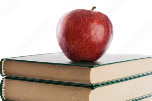 A red apple on top of books on a white background