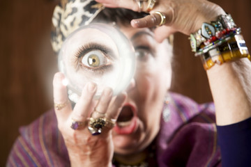 Female gypsy fortune teller holding a crystal ball to her eye