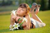 Attractive girl lying on the grass sensing flower poster