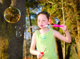Young girl in woods blowing big bubbles