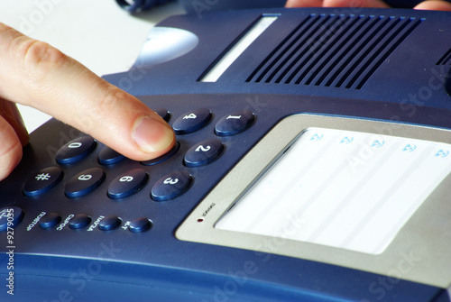 finger with  blue telephone keypad