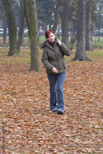 Redheaded backpacker girl walking in an autumn park.