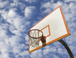 A basketball ring over a blue sky with clouds.