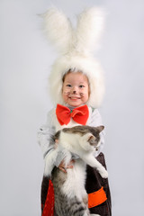 Small Girl in the costume of rabbit holds by the hands of tomcat