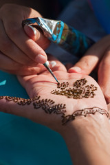 A temporary henna tattoo applied by an artist