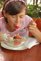 A portrait of a young girl eating salad