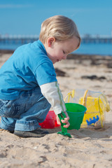 A young boy building sand castles on the beach.