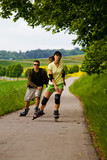 a couple ride rollerblades in the park