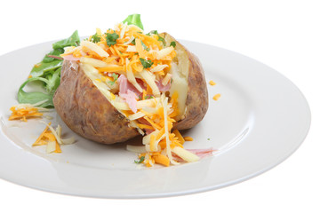 Baked potato filled with ham and cheese with watercress salad