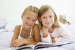 Two Young Girls In Their Pajamas, Reading A Book