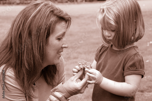 small child takes flower from mother