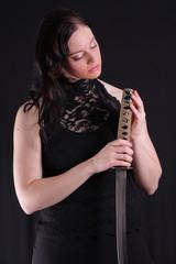 Young woman holding a samurai sword, katana, against black