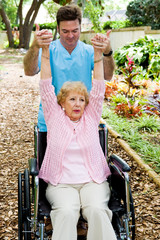 Physical therapist helping a disabled senior woman