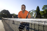 Man playing tennis holding sracket near net.  Horizontal