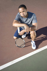 Tennis player crouching down looking defeated . Vertical