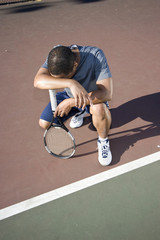 Tennis player crouching down looking defeated. Vertical