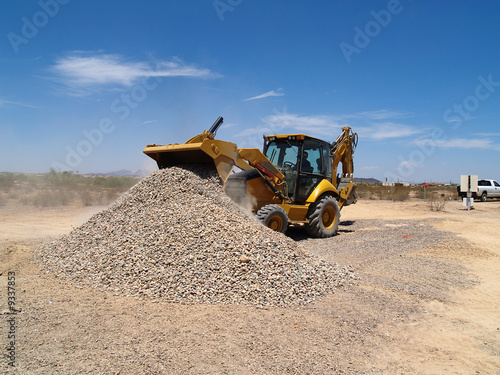 backhoe shoveling and dumping gravel.  Horizontal