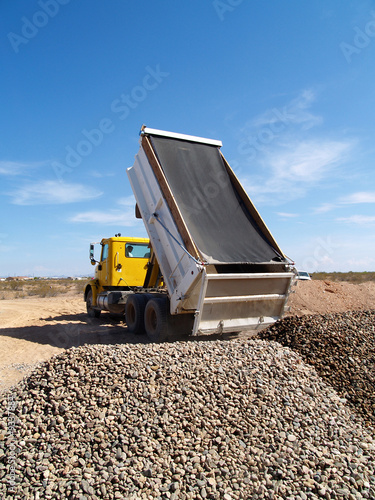 A dump truck dumping gravel on excavation site.   Vertical.