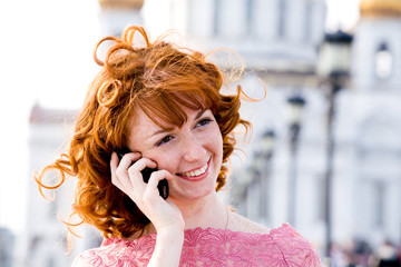 Smiling red-haired young woman talking on mobile phone