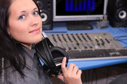 A young smiling woman in radio studio