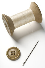 a spool of thread, needle and button on white