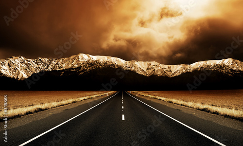 canvas print picture Long straight road heading to stormy mountains