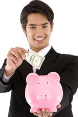 Business man putting a bill on his piggy bank -