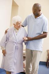 Nurse Helping Senior Woman To Walk