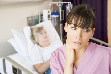 Nurse Standing In Hospital Room,Looking Tired
