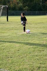 Five year old boy kicking soccer ball at park.